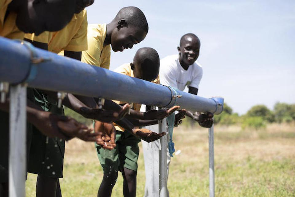 Students and teacher Jonoka Akai (far right) wash their hands with water from the newly rehabilitated borehole outside Dumak Primary School in Torit.