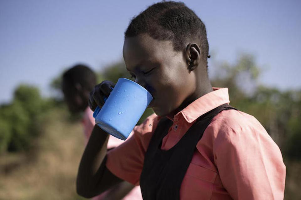 Keziah, 14, drinks water from the borehole at AIC Nursery and Primary School in Torit.