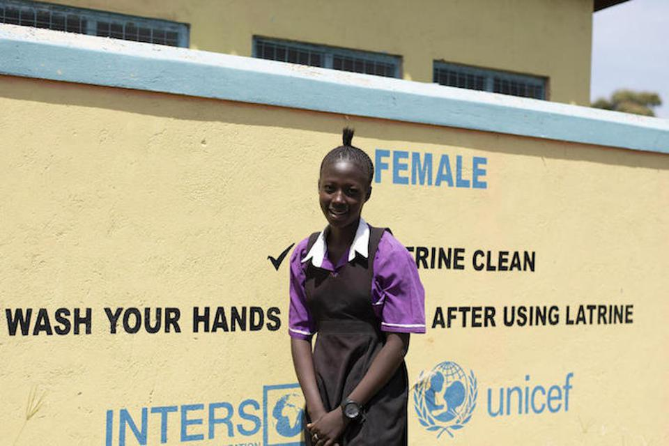 Sixteen-year-old Jasmine Blessing stands outside the newly constructed latrine block at Torit West Primary School.