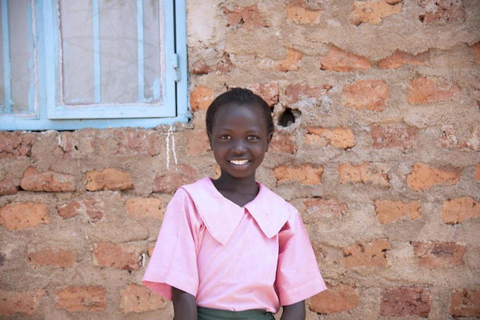 Ten-year-old Lino stands outside her brick-walled school in Torit, South Sudan, wearing her pink school uniform.