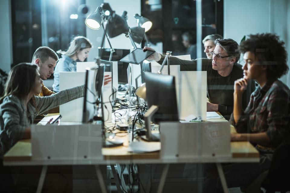 Large group of computer programmers working late at corporate office.