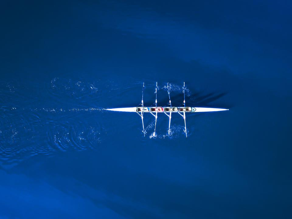 Aerial view of a rowing boat surrounded by classic blue water