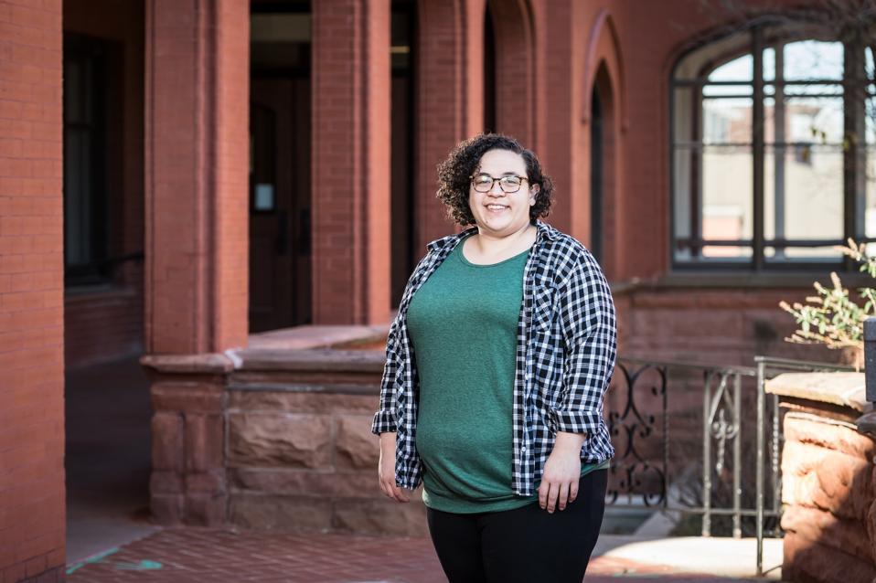 Amanda DoAmaral standing in front of school building
