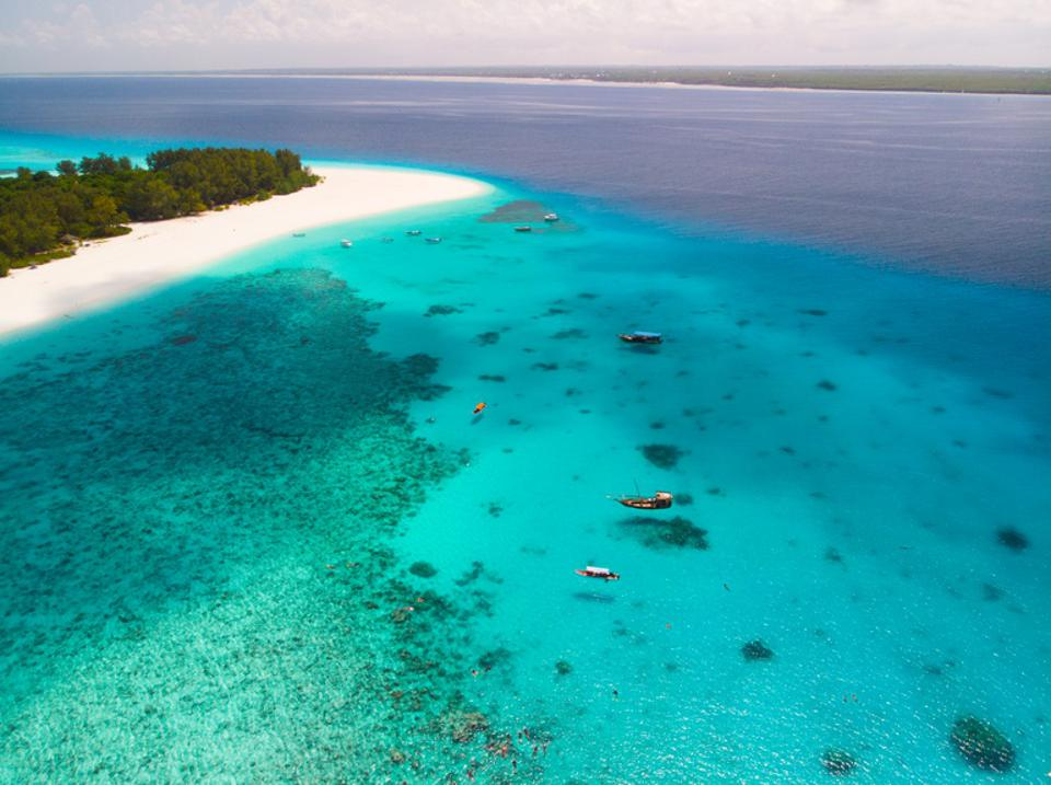 A few boats and snorkelers float in the clear waters over the coral reefs of Mnemba Atoll; a white sand beach with tress in in the background.
