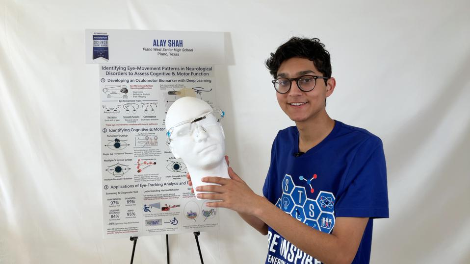 Alay Shah, an Indian-American teenager, holds up a foam head with eye-tracking glasses on