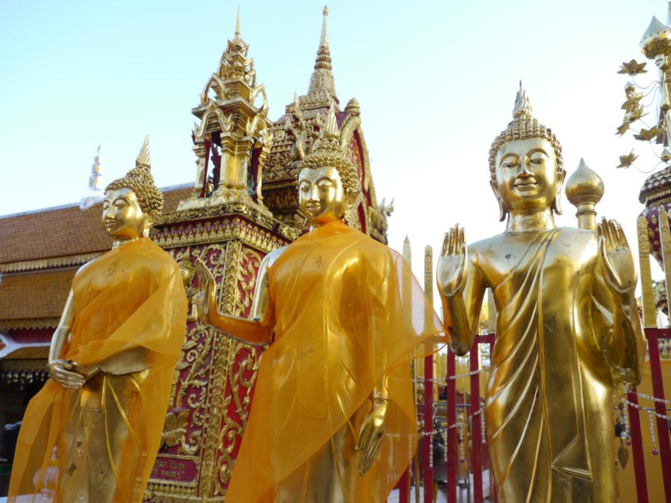 Three serene-looking gold-plated Buddha statues, two draped in orange cloth, in front of a gold-plated temple