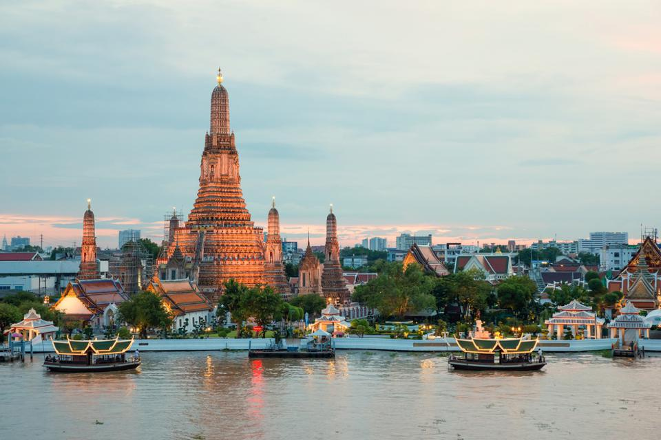 Wat Arun towers above other buildings next to the river with a few Thai boats in the foreground