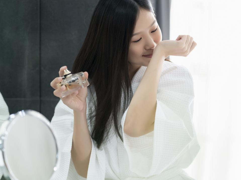 beautiful asian woman in white bathing dress enjoy good smell of new perfume bathroom background