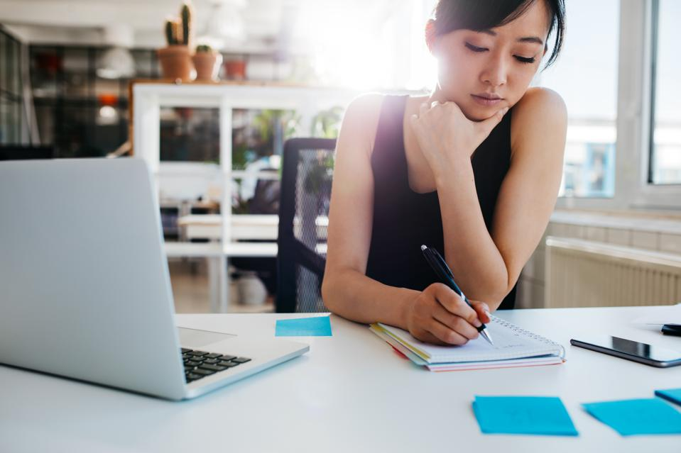 Asian female professional writing notes - thinking of the next career move?