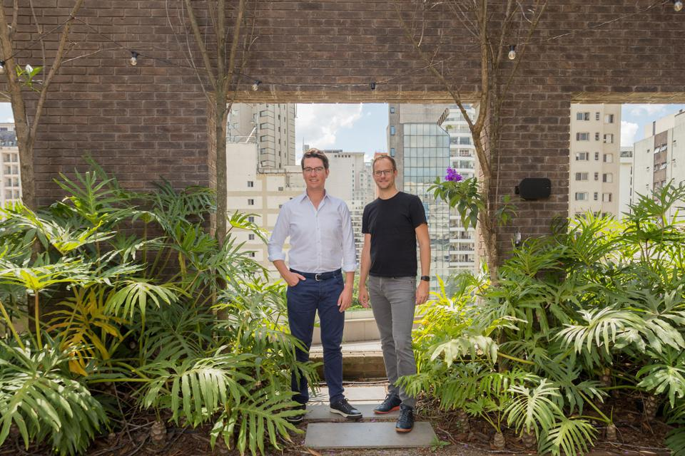 Two white men standing in a doorway with buildings in the horizon, surrounded by plants