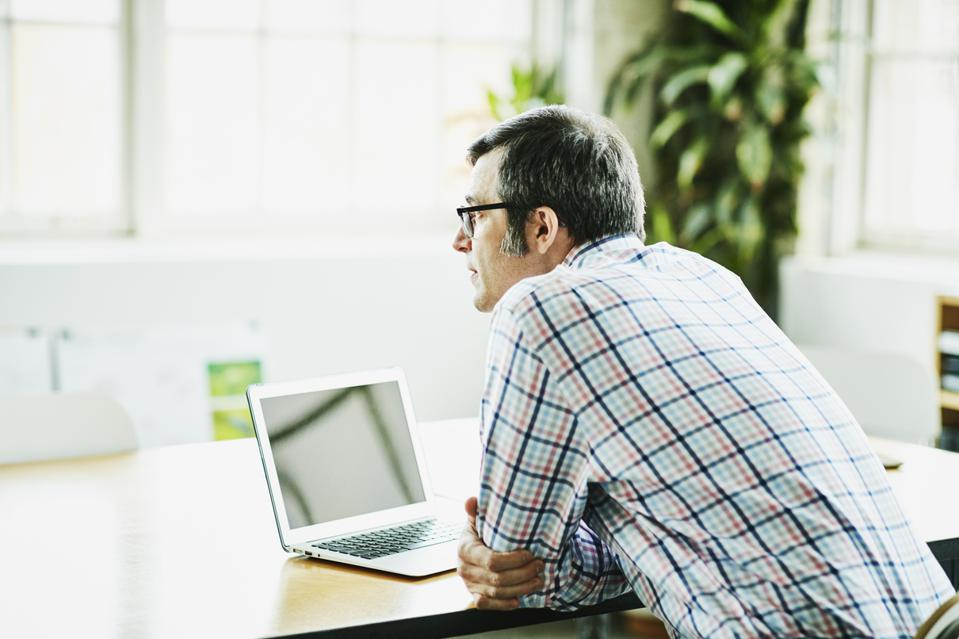 Businessman sitting at office conference table working on laptop