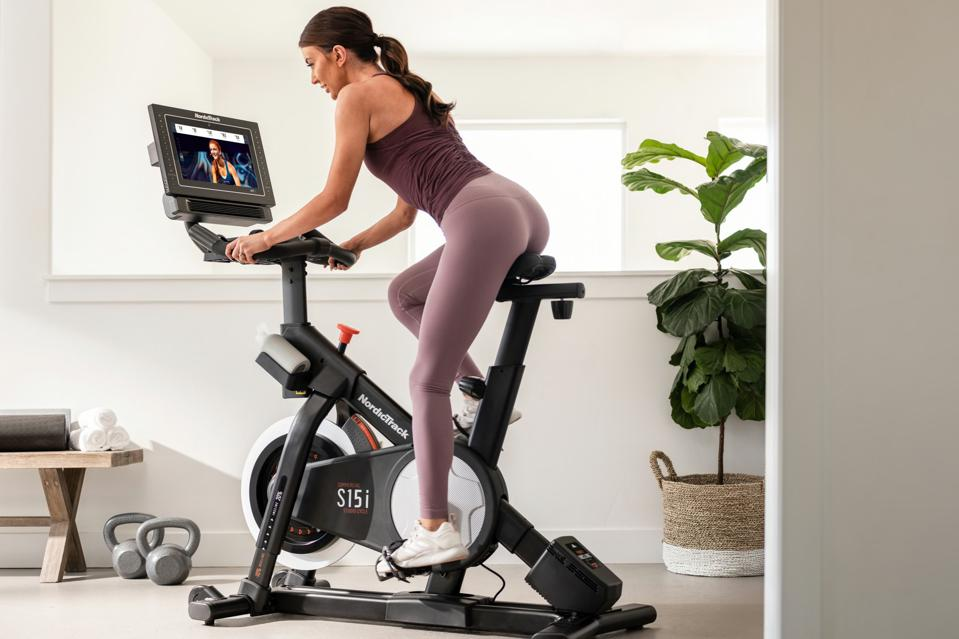 Woman riding a NordicTrack Commercial S15i spin bike with her back to the camera