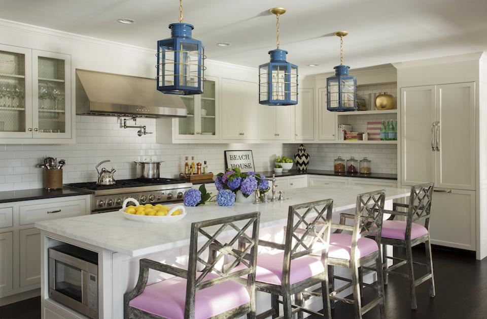 A white kitchen with stainless steel appliances and blue light fixtures