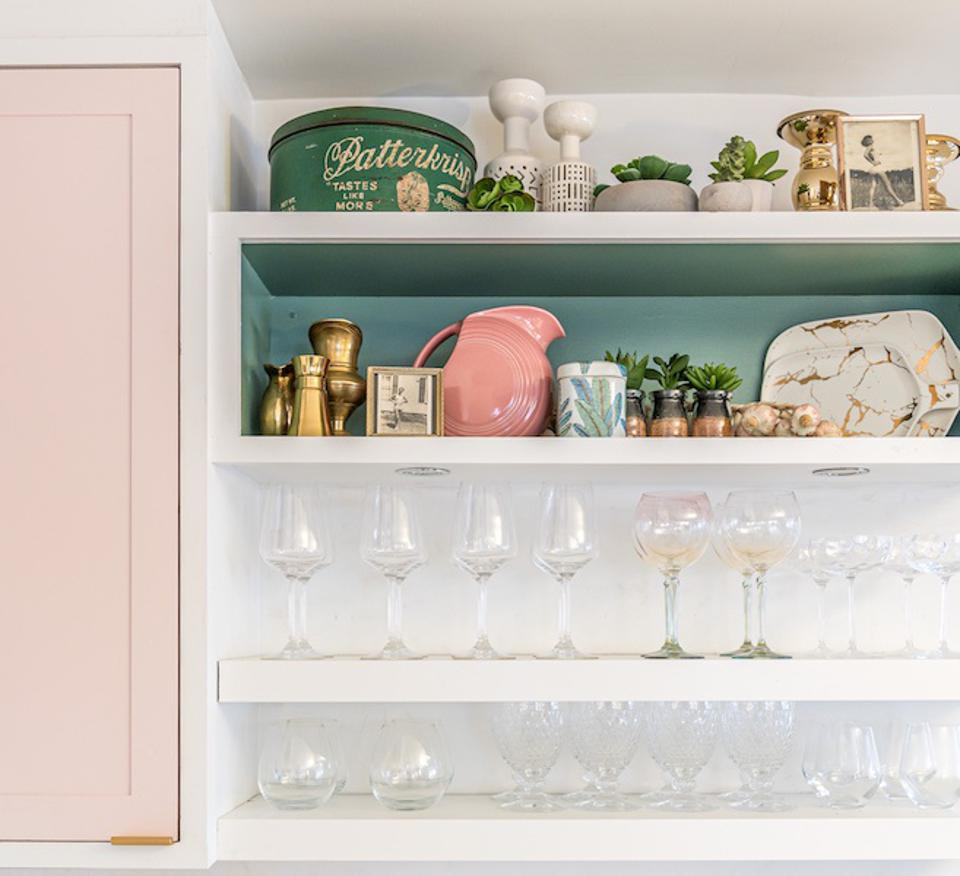 A kitchen shelf with pink cabinetry and a turquoise painted backsplash.