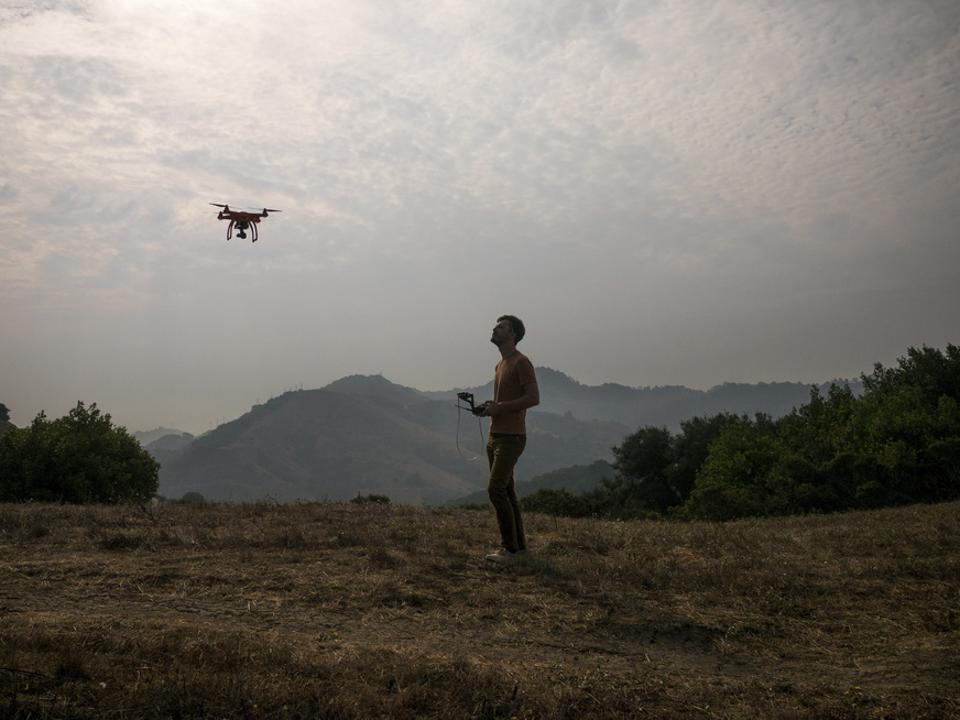 Side view of man operating drone through remote control against mountains