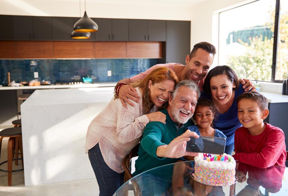 Multi-Generation Hispanic Family Celebrating Granddaughter's Birthday At Home