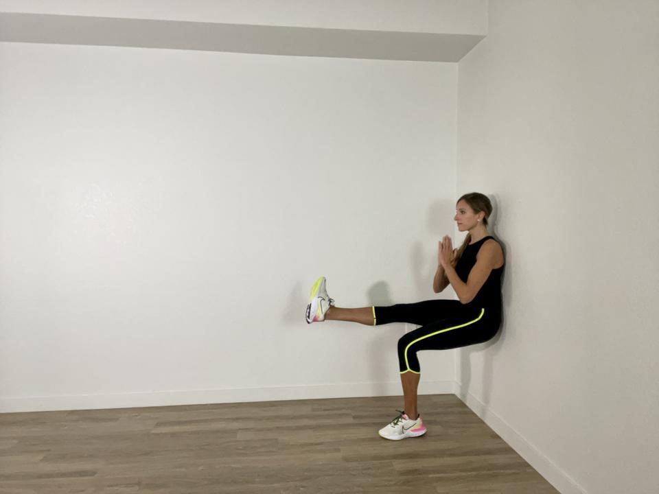 Single leg wall squat against a hotel room wall