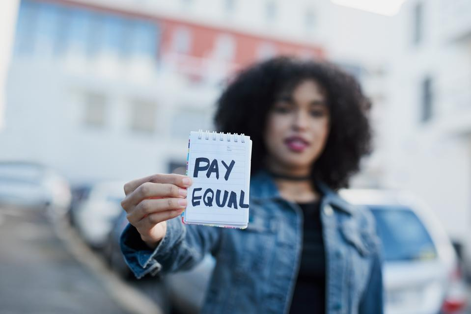 Shot of an unrecognizable woman holding a note pad written ″PAY EQUAL″ in the city