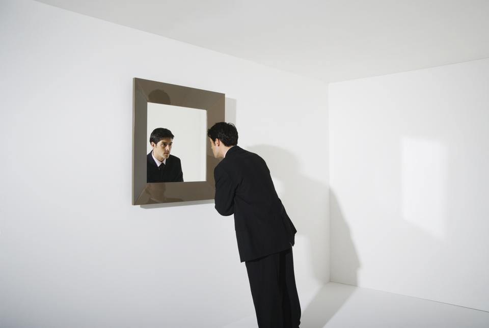 Businessman looking at reflection in mirror on wall