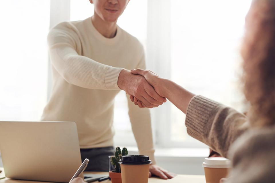 two people shaking hands across a desk
