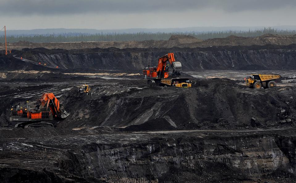 Orange and yellow mining vehicles operate in a black and grey open cast mine in Canada.