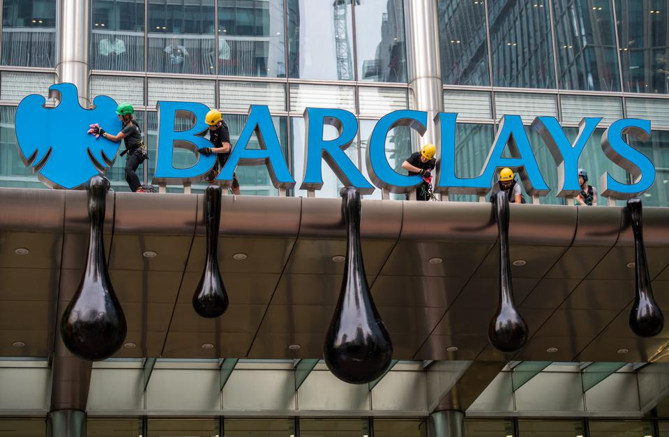 Greenpeace campaigners decorate a Barclays bank sign with huge black oil droplets.