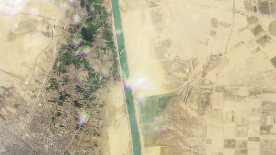 A wide shot shows the Ever Given blocking the Suez Canal, not allowing other traffic to move through the critical shipping channel.