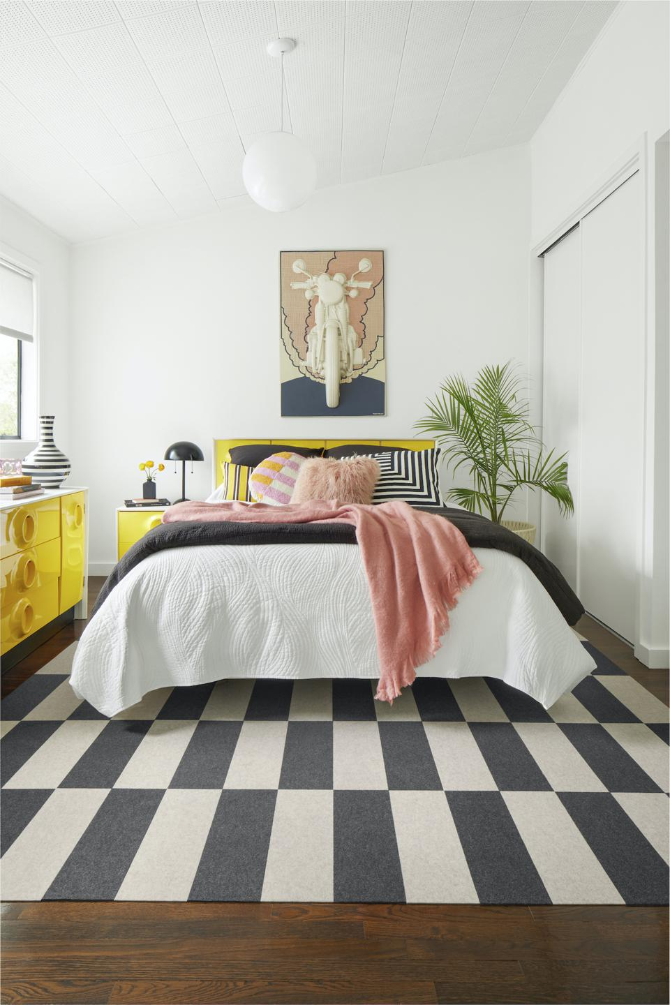 Alternating colors in this checkerboard design from FLOR makes an interesting area rug in the bedroom.
