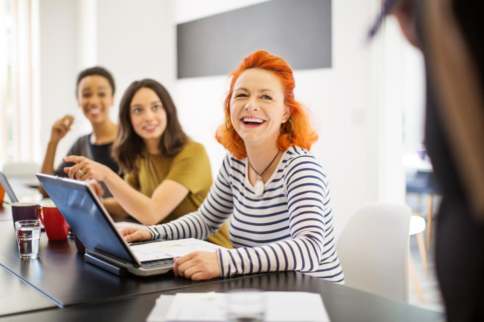 Mature woman smiling in meeting with colleagues