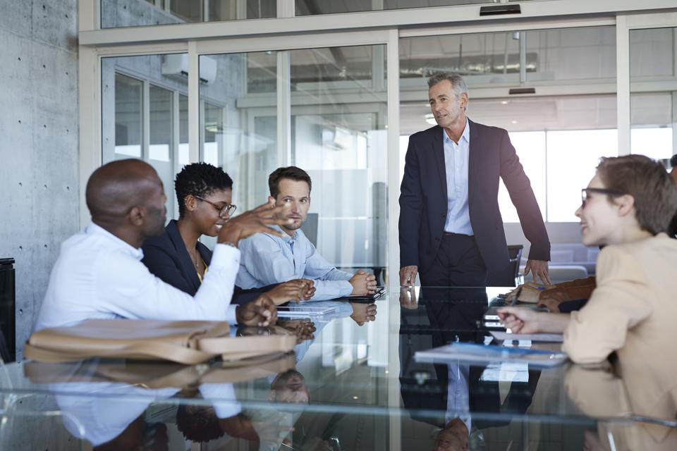 Male leader at head of conference table with diverse group of leaders in conversation