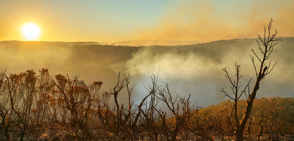 Sun setting in burnt smouldering mountain landscape with smoke filled valley