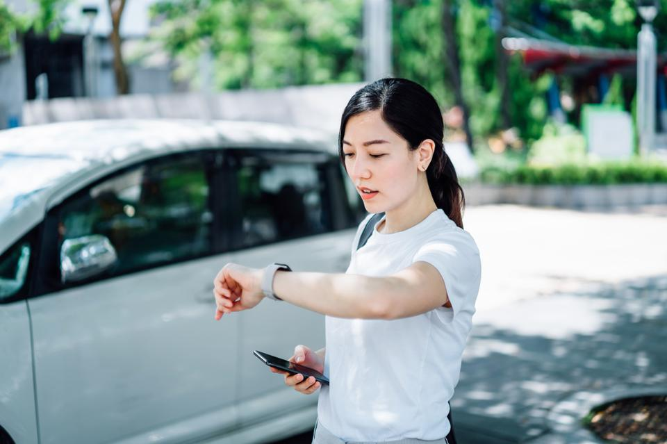 Young Asian woman being late and in a hurry. She is checking time on smartwatch while waiting for the pick up by the reserved crowdsourced taxi. Business on the go concept