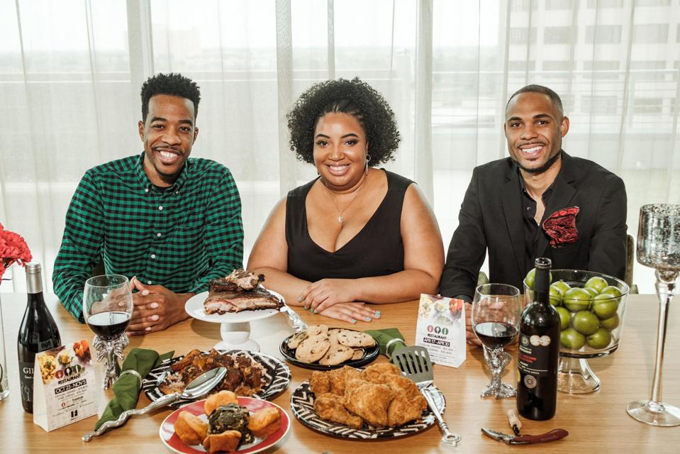 Three people smiling and sitting a table set with many plates of food
