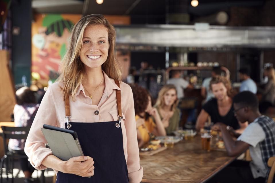 Portrait Of Waitress Holding Menus Serving In Busy Bar Restaurant