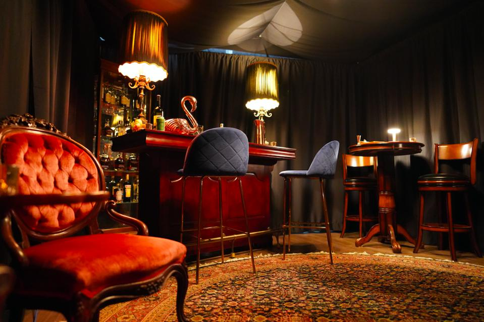 a dark cozy prohibition themed bar with velvet seats and sultry decor