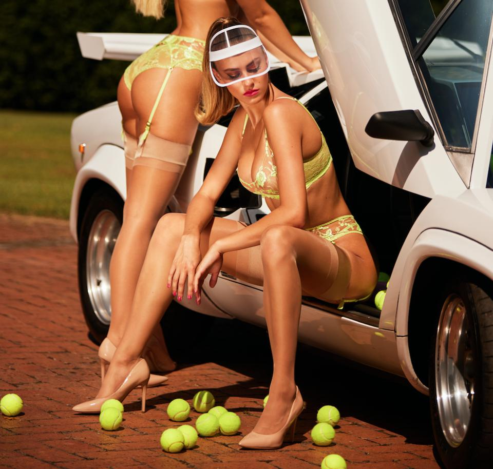 two models in lingerie wearing visor hats and heels with tennis balls around