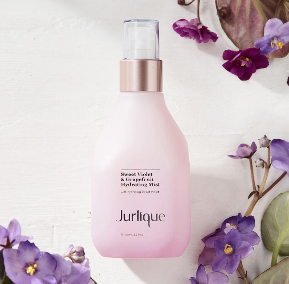 a bottle of skincare surrounded by purple violet flowers
