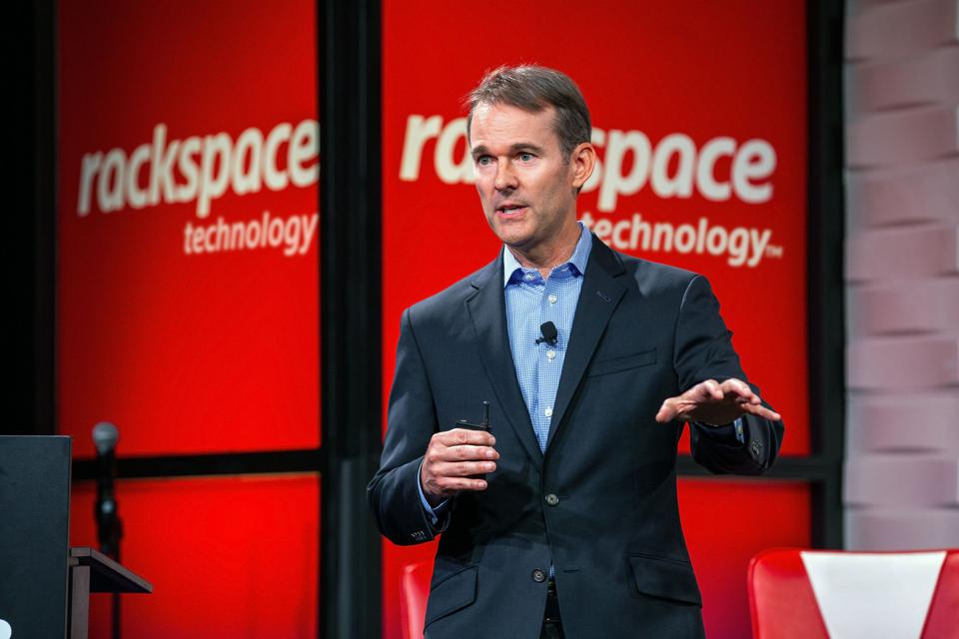 Kevin Jones, CEO of Rackspace Technology, standing, making a presentation