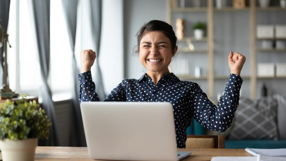 Euphoric young indian girl celebrate online victory triumph with laptop