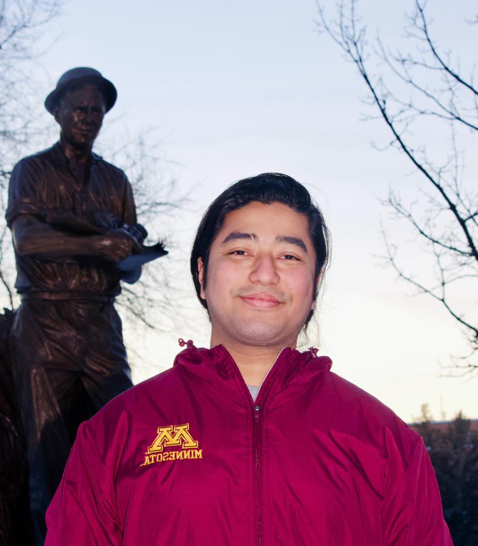 Zenith Tandukar, Ph.D. Candidate at University of Minnesota, with a statue of famous agronomist Norman Borlaug.