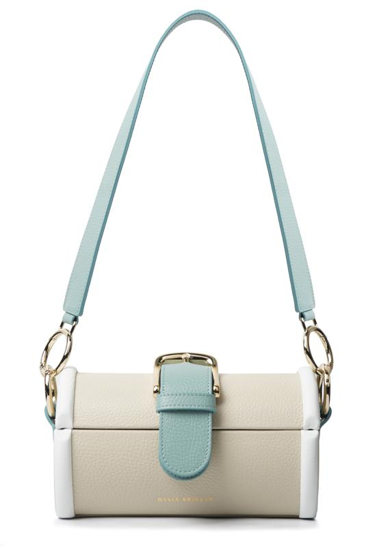 The MOE - Lamb/ Aqua/ White, crafted from Italian cow leather, is a vintage-inspired box bag featuring a large buckled belt across the front and chunky hardware. Magnetic flap-clip closure, light gold-tone hardware, two straps, 100% made in Italy.