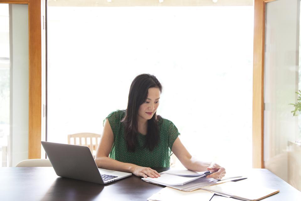 Korean woman paying bills on laptop