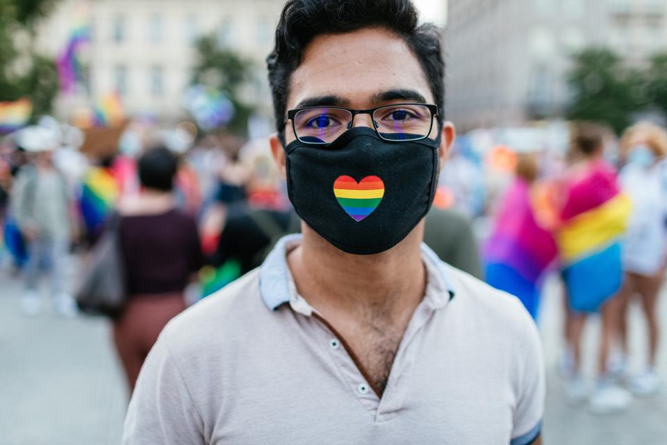 A participant wears a surgical mask with a rainbow-coloured...