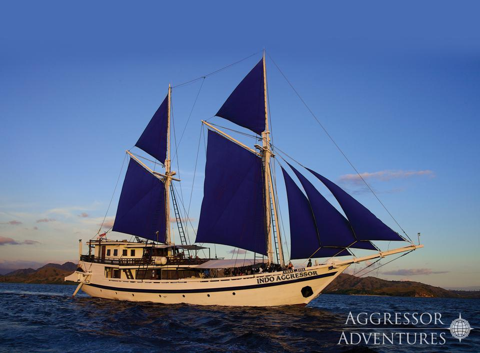 A two-masted blue-sailed boat on a dark blue sea