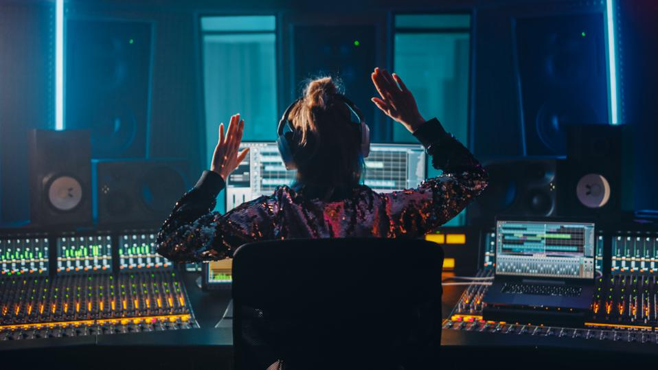 Artist, Musician, Audio Engineer, Producer in Music Record Studio, Uses Control Desk with Computer Screen showing Software UI with Song Playing. Celebrates Success with Raised Hands, Dances. Back View