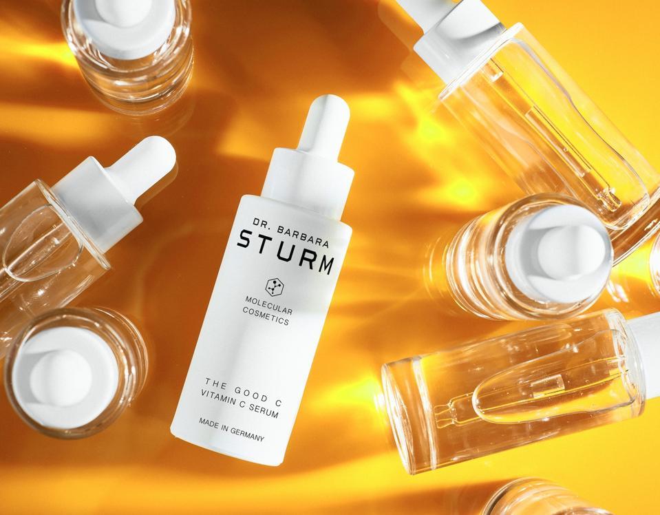 a white bottle of serum on orange background
