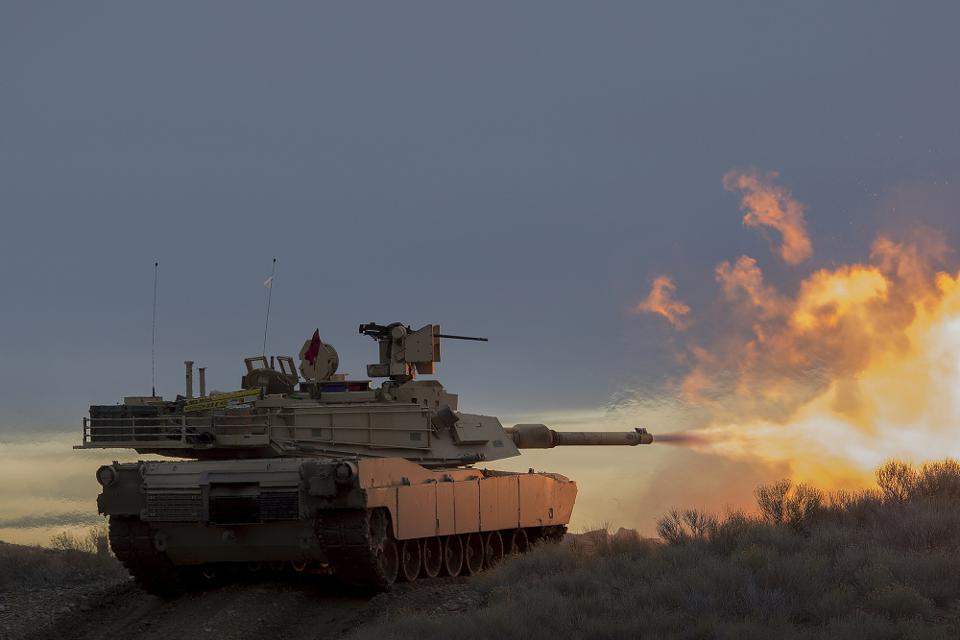 Abrams tanks in a training exercise at dusk.
