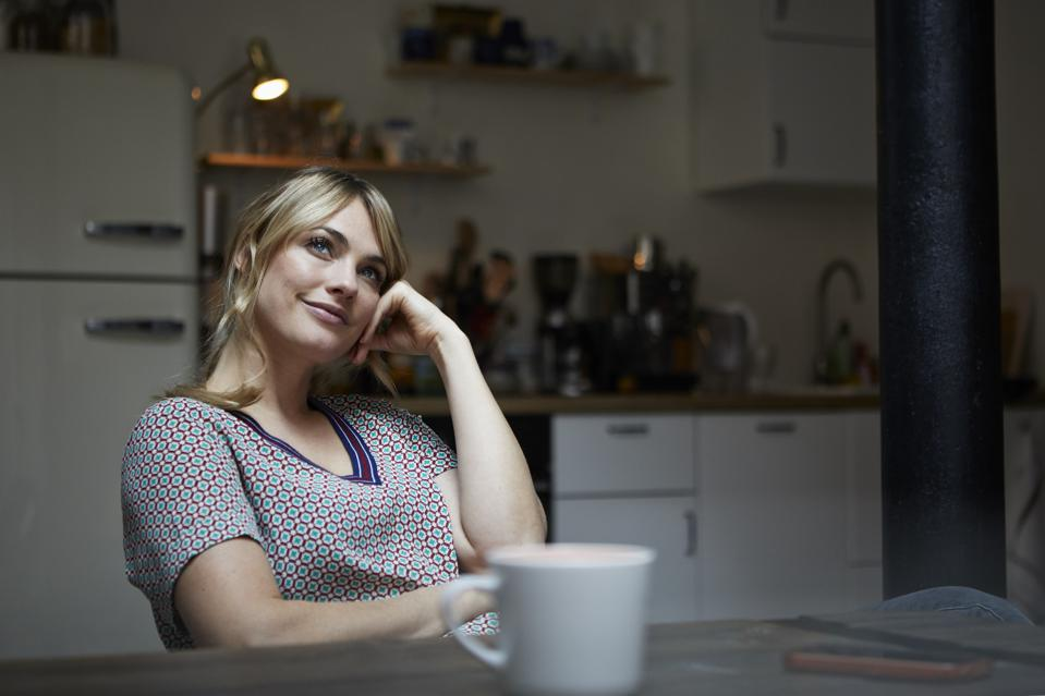 Portrait of daydreaming woman sitting at table in the kitchen