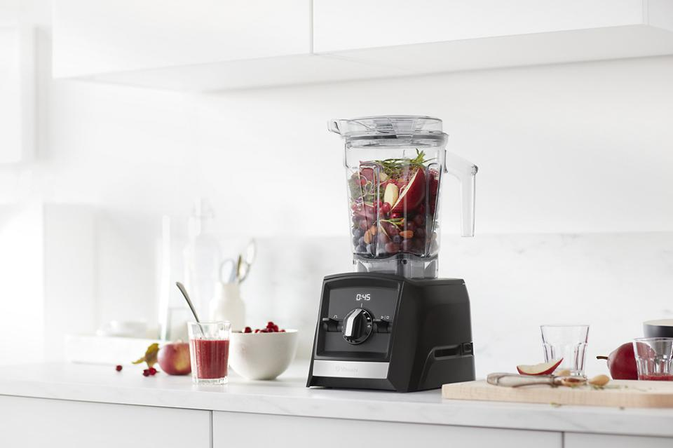 Vitamix blender filled with fruit in a white kitchen