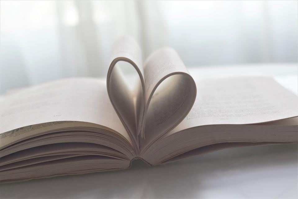 An opened book with pages folded to look like a heart.